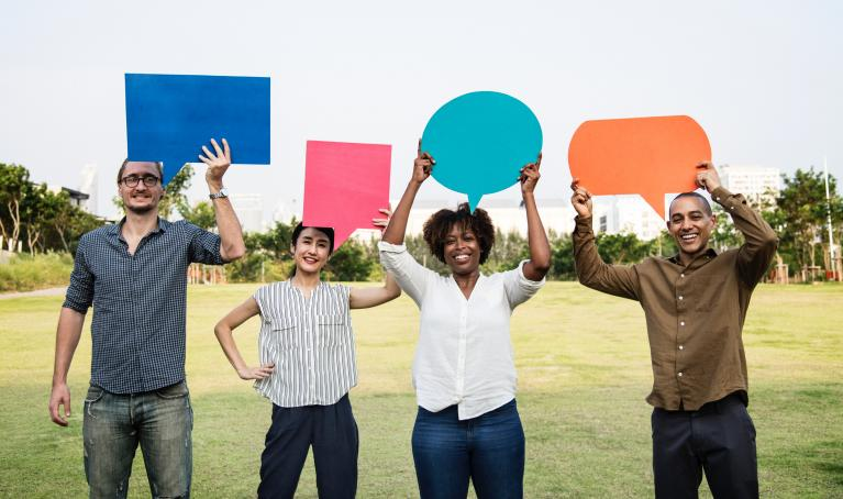group of people holding up cardboard speech bubbles